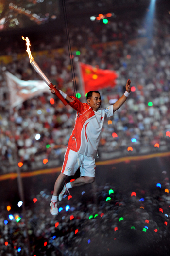Digital photograph of torch bearer aloft in Beijing stadium