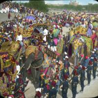 Parade with elephants carrying people, military band with Delhi Fort in background