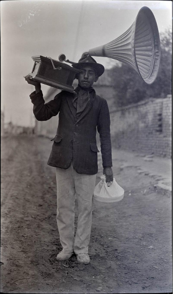 Image of man in uniform carrying a gramophone on his shoulder