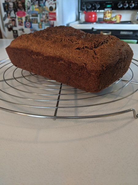 A brown rectangular loaf of bread cools on a wire rack on a white kitchen counter.