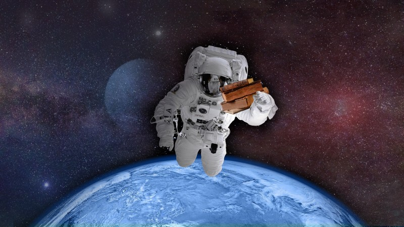 astronaut in space holding old books with earth in the background