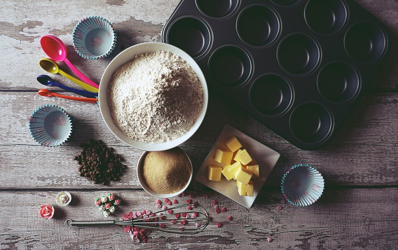 Image of an assortment of baking utensils, a bowl of flour, sugar, and butter as well, arranged on a woodent table