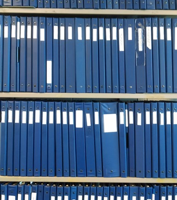 Photo of blue binders on shelves in Special Collections Reading Room