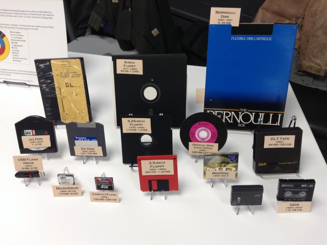 A table display of 15 vintage floppy disks and other forms of digital storage media