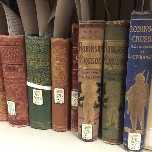 Copies of various editions of Robinson Crusoe on the shelves