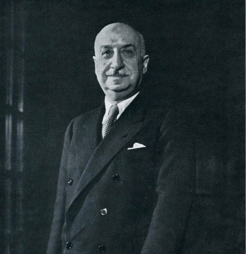 Black and white portrait of De Marinis in double-breasted suit