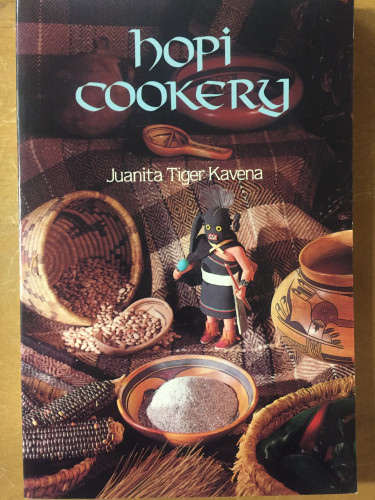 front cover of Hopi Cookery, depicting a small figure perched among bowls, baskets, and recipe ingredients