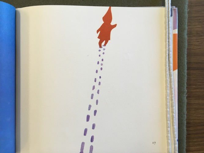 page from The Snowy Day depicting a small child walking through the snow with a long trail of footprints