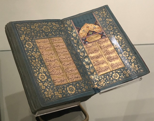 View of Islamic Manuscript 350 on display with illuminated opening featured