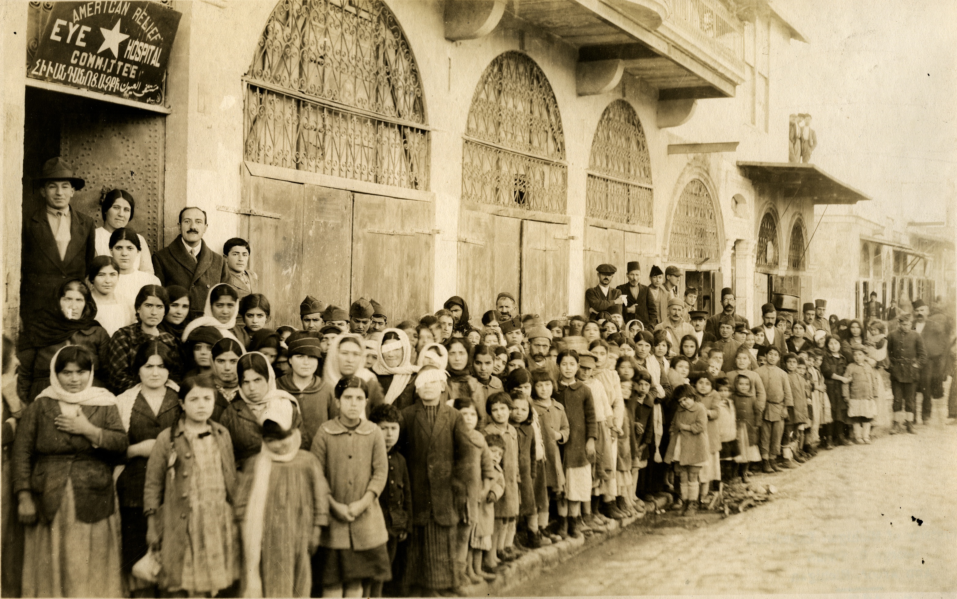 Line-up at the entrance to the A.C.R.N.E eye hospital, on the sidewalk. Dr. Tenner at right of door in back row at the left. January 7, 1920. Aleppo, Syria. Photograph by George R. Swain. Courtesy of the Kelsey Museum