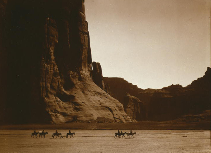 Photograph of a number of people on horseback roaming the an old west landscape.