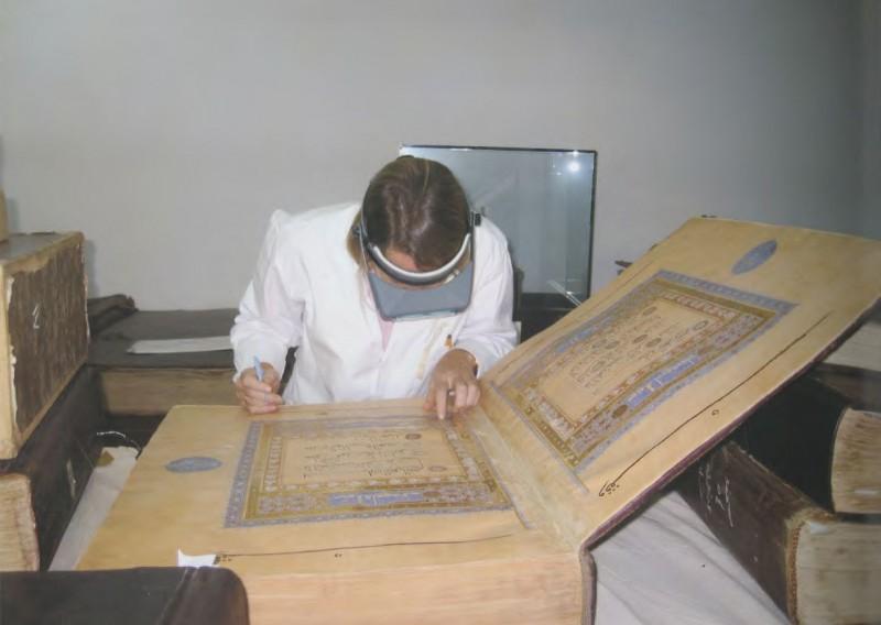 conservator in white coat examines massive manuscript volume