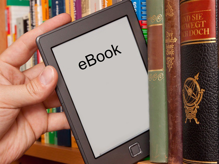 eReader being pulled off a shelf of books