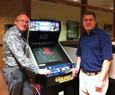 A photograph of two men standing next to an arcade cabinet
