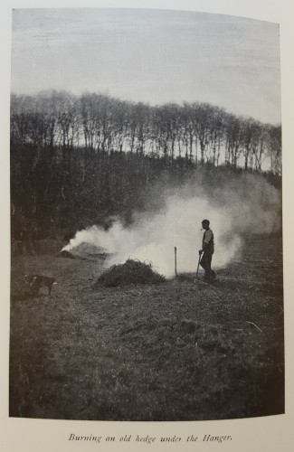 Black and white photograph of a man standing over a smoking fire, against a skyline of leafless trees