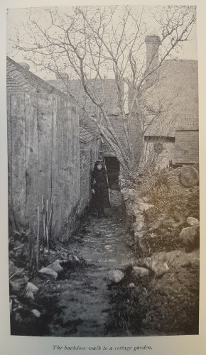 Black and white photograph of a girl standing in a narrow path to a cottage door.