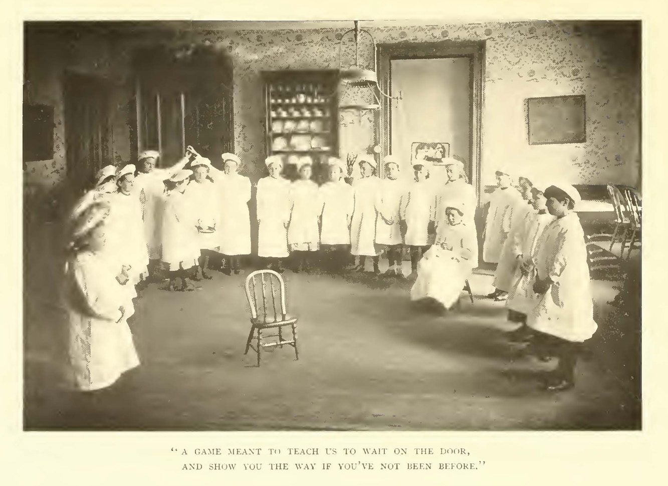 A group of girls in white smocks and caps stand around a chair in a 1901 classroom.