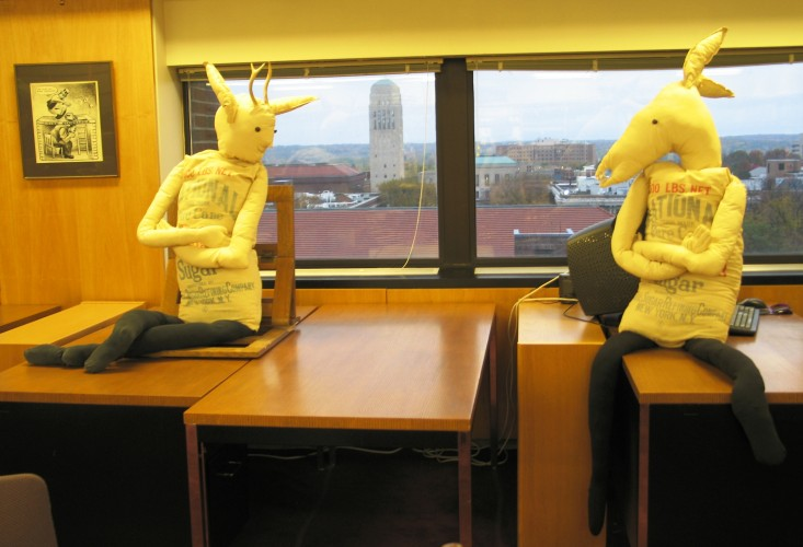 Two nearly-human sized figurines made of floursacks with animal heads, sit on top of tables in front of a window