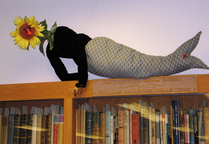 Figurine with a mermaid tale and a sunflower head, lounging on top of a bookcase