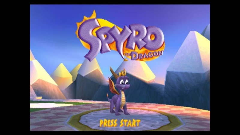 "The title menu screen for the Playstation 1 game, ""Spyro the Dragon"". In it stylized purple text reading ""Spyro"" in large letters and ""The Dragon"" in smaller letters are written on a circular, orange background. The majority of the image surrounding it shows a low-poly, blue-ish sky with what appear to be snow-capped mountains in the background. Beneath the title is the titular character, Spyro, who is a small purple dragon with red-orange wings, brown horns, and an orange fin on his head. The words ""Press Start"" are shown below Spyro in Yellow"