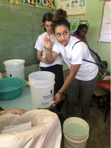 Student participant explains how to clean and use the water filter to the teachers