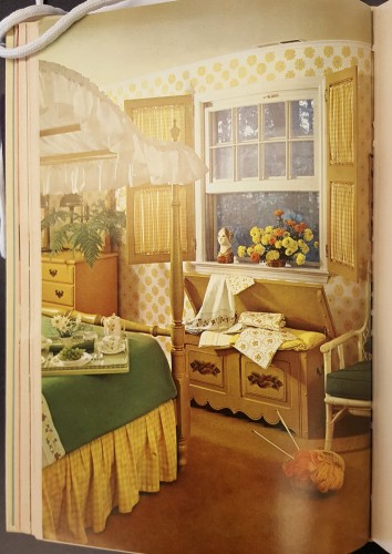 Bedroom decorated in yellow and green: yellow checked curtains set in wooden shutters, a yellow, green and white canopied bed, and a wooden chest storing yellow and white linens.