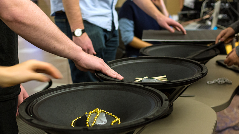 Several students place their hands on loudspeakers filled with percussion instruments.