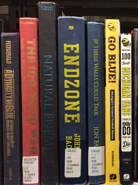 Picture of spines of books about Michigan football history in the Hatcher Graduate library.