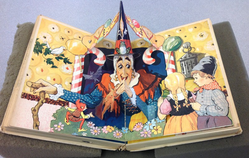 Pop-up of Hansel and Gretel meeting the witch at her house made of cake and candy