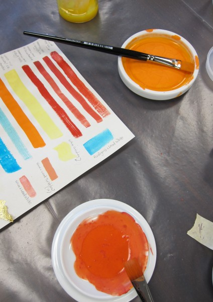 Paper with strokes of brightly colored pigments, dishes with paints and brushes, arranged on a table