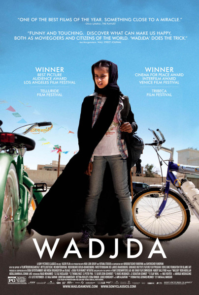 Middle Eastern young girl stands against a blue sky, between two bicycles, wearing jeans, a tee shirt and a dark cloak.