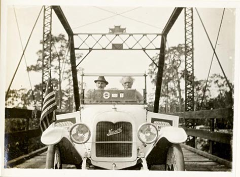 photo of two men driving a car on a bridge