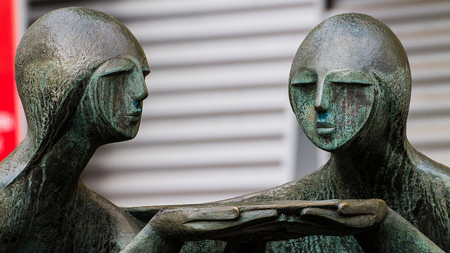 Two statues jointly holding a plate
