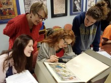 Students and professor looking at book, as described in caption.