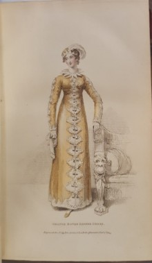 Woman standing, wearing an orange dress with white fan-shaped decorations down the front.