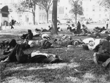 Black and white photograph of people lying on the grass among trees. Stone buildings in background.
