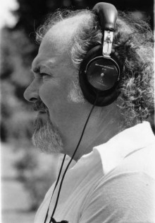 profile headshot of an older person with light skin, grey and white facial hair, and curly grey hair wearing headphones and a white collared shirt