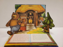 Pop-up page spread showing the three bears leaving on a walk, with a young blonde girl (Goldilocks) peeking out from behind a tree
