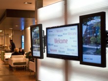 "Digital displays in foreground say words ""Welcome"" as students sit in background of Bert's Study Lounge."
