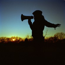 Silhouette of a woman with a megaphone.