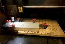A tabletop carving machine cuts through a piece of linoleum.