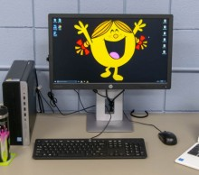 Picture of a workstation with a happy cartoon character as the desktop image