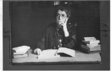 Black and white photograph of Emma Goldman sitting at a desk surrounded by books