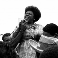 Black and white photograph of Fannie Lou Hammer. Three quarter photo of Black woman holding and speaking into a speaker microphone. The heads of other people can be seen around her waist.