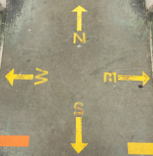 Image of a yellow compass painted on the floor of the Hatcher Library's North Stacks, with arrows pointing outward to the four directions.