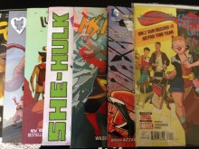 Photograph of seven comic books laid out on top of one another. From bottom to top, they are Faith, Rat Queens, Lumberjanes, She-Hulk, Ms. Marvel, Wonder Woman, and The Unbeatable Squirrel Girl.
