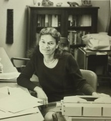 Photograph: Portrait of Eleanor Burke Leacock sitting at a desk, with a book case visible behind her.
