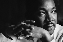 Black and white photograph of Dr. Martin Luther King. Black male seen from shoulders up, looking off to the left with hands folded in front of him.