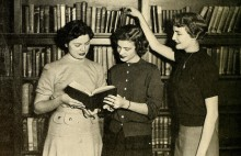 Three women reading a book together in a library setting