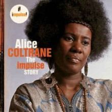 Album cover featuring a portrait photograph Alice Coltrane, a Black woman with an afro wearing large dangling earrings. She is not looking at the camera.